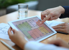 Real-estate agent showing house plans. On electronic tablet Royalty Free Stock Photos