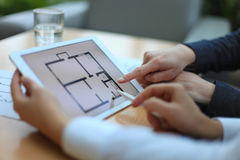 Real-estate agent showing house plans. On electronic tablet Royalty Free Stock Images