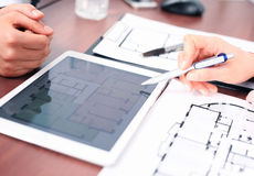 Real-estate agent showing house plans. On electronic tablet Royalty Free Stock Photography