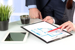 Real-estate agent showing house plans to a businesssman. Focus on a pen and hand Royalty Free Stock Photos