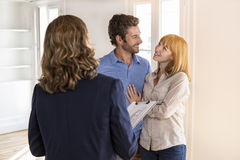 Real estate agent showing modern white apartment to future owners. Happy young couple visiting a flat with realtor Royalty Free Stock Image