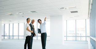 Real estate agent showing new office space to clients. Male real estate agent showing new office space to clients. Business people discussing and looking at new royalty free stock images
