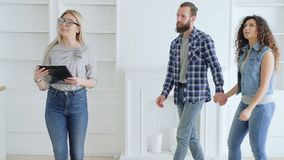 Real estate agent young couple new modern home. Real estate agent showing young couple modern apartment. Bearded hipster guy and curly girl curious about new stock video