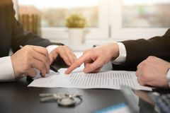 Real estate agent signing a contract buy-sell home. Real estate agent signing a contract buy-sell house. Two men sitting at the desk, home insurance policy on royalty free stock images