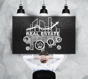 Real estate agent is sitting in front of chalkboard with the sketch of the opportunities of real estate market. Royalty Free Stock Photography