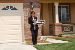 Real Estate Agent - Sold Sign. Beautiful Real Estate Agent in front of home holding Sold sign Stock Image