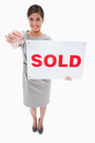 Real estate agent with sold sign handing over key. Against a white background royalty free stock photo