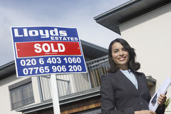 Real Estate Agent By Sold Sign Outside House. Portrait of a happy and confident female real estate agent standing by sold sign outside house Royalty Free Stock Photo
