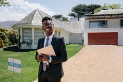Real estate agent standing outside a house for sale. Portrait of confident young african male real estate agent standing outside a house for sale. Realtor with royalty free stock photography