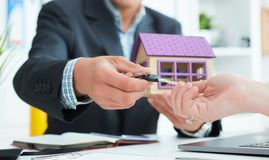 Real estate agent in suit holds house model in one hand and in the second hand holds out the keys of the house to woman. Royalty Free Stock Photos