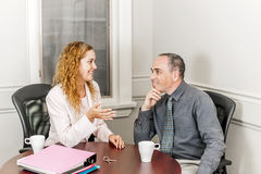 Real estate agent talking to client. Female real estate agent talking to new home owner in office meeting room royalty free stock photos