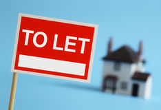 Real estate agent to let sign. With house in background Royalty Free Stock Photo