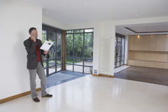 Real Estate Agent Using Cellphone In New Property Stock Photos
