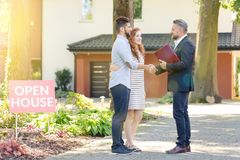 Real estate agent welcoming visitors. Real estate agent welcoming young visitors coming to open house Royalty Free Stock Photo