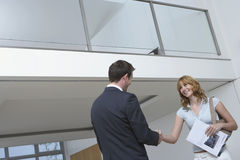 Real Estate Agent And Woman Shaking Hands In New Home Stock Photography