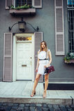 Real estate agent woman standing in front of the townhouse. Royalty Free Stock Images