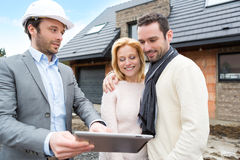 Real estate agent and a young couple in front of future home Royalty Free Stock Photo