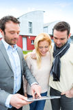 Real estate agent and a young couple in front of their next home Stock Photos