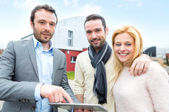 Real estate agent and a young couple in front of their next home Royalty Free Stock Photos