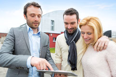 Real estate agent and a young couple in front of their next home Royalty Free Stock Photo