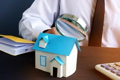 Real estate assessment. Man looking through magnifying glass on model of house. Royalty Free Stock Photos