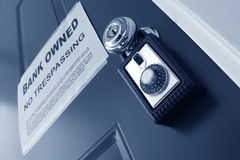 Real Estate Bank Foreclosure Notice and Lock Box. Real estate combination lock box on foreclosed house door with bank owned lender foreclosure notice (fictitious royalty free stock photo