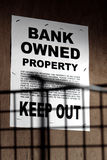Real Estate Bank Owned Sign on Boarded Up Building. Grunge Real estate lender bank owned keep out sign notice posted on a boarded up foreclosed building in royalty free stock images