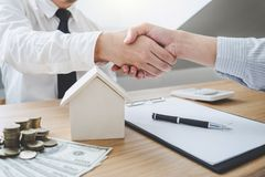 Real estate broker agent and customer shaking hands after signin. G contract documents for ownership realty purchase, Concept mortgage loan approval stock image