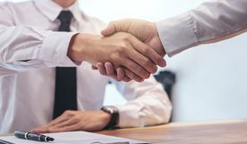 Real estate broker agent and customer shaking hands after signin stock images