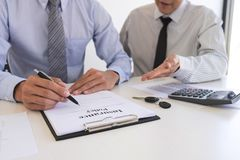 Real estate broker agent presenting and consult to customer to decision making sign insurance form agreement, home model, stock photo