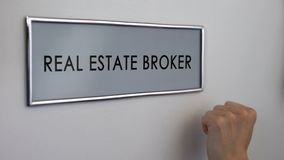 Real estate broker office door, hand knocking closeup, apartment purchase deal. Stock photo royalty free stock photography