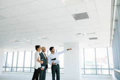 Real estate broker showing office space to clients. Business people and real estate agent at empty office space, with estate broker pointing at something royalty free stock image