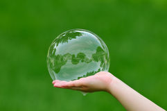 Real Estate Bubble. Child holding soap bubble with house reflection. Real estate bubble concept Stock Photography
