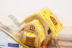 Real estate business concept. Model of toy house placed on Euro. Banknotes Royalty Free Stock Photos