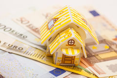 Real estate business concept. Model of toy house placed on Euro. Banknotes isolated Stock Photos