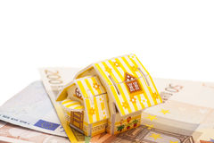 Real estate business concept. Model of toy house placed on Euro. Banknotes isolated Stock Image