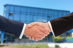 Real estate or business handshake over office building. Real estate or business handshake over blue office building made of glass and windows Stock Image
