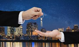 Real estate business, residential rental and investment. Businessman handover keys, with city at night in Japan backgrounds royalty free stock images