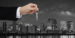 Real estate business, residential rental and investment. Businessman handover keys, with city at night in Japan backgrounds stock photos