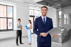 Realtor with folder and customers at new office Stock Image