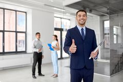 Realtor with folder showing thumbs up at office. Real estate business, sale and people concept - happy smiling realtor or businessman with folder showing thumbs Stock Images