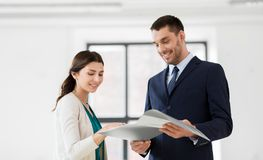 Realtor with folder showing documents to customer. Real estate business, sale and people concept - happy smiling realtor with folder showing documents to female stock images