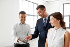 Realtor showing tablet pc to customers at office Royalty Free Stock Photos