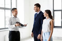 Realtor showing contract document to customers. Real estate business, sale and people concept - male realtor with clipboard and pen showing contract document to Stock Photos