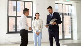 Realtor with folder showing documents to customers. Real estate business, sale and people concept - realtor with folder showing documents to customers at new stock footage