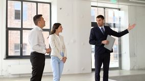 Realtor showing new office room to customers. Real estate business, sale and people concept - realtor with folder showing new office room to customers stock footage