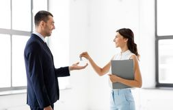 Realtor giving key to customer at new office stock images