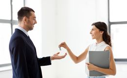 Realtor giving key to customer at new office stock photography