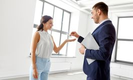 Realtor giving key to customer at new office stock image