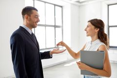 Realtor giving key to customer at new office stock photo